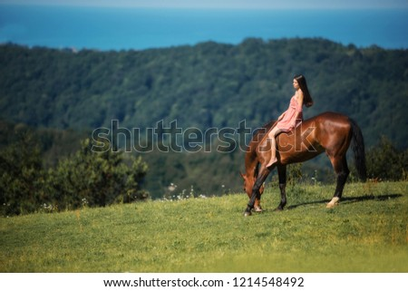 girl sitting on a horse on the background of mountains #1214548492