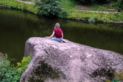 Girl sitting on a huge stone in front of the lake and looking at the water, view from the back, dendrological park Sofiyivka, Uman Ukraine.