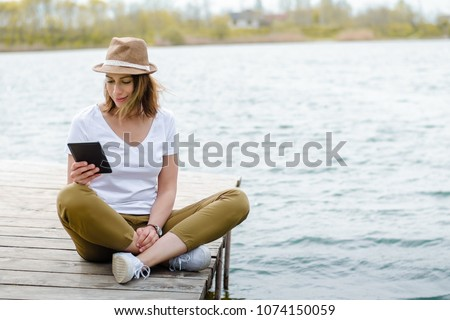 Girl sitting on a lake jetty, reading e-book from e-reader device.
