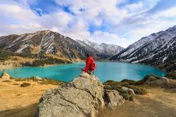 girl sitting on a mountain, mountain lake,Big Almaty Lake, Kazakhstan, Almaty