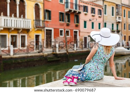 girl sitting on a pier near the canal in venice. Italy