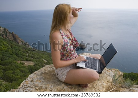 Girl sitting on a rock beside the sea with a laptop