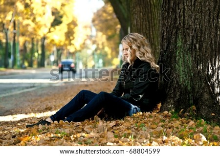 Girl sitting on a street in autumn leaves