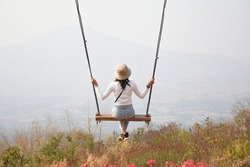 Girl sitting on a swing watching the scenery. Loei, Thailand
