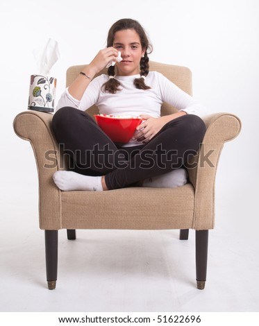 Girl sitting on an armchair with a popcorn bowl with a pack of paper tissue