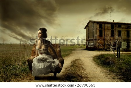girl sitting on armchair in the countryside