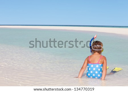 Girl Sitting On Beach Wearing Snorkel And Flippers