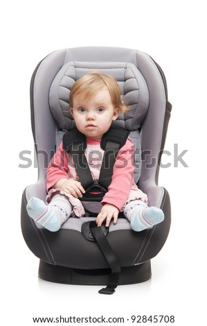 girl sitting on child's car seat - isolated on a white background
