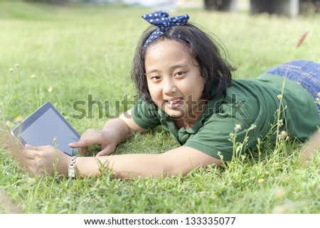 girl sitting on green grass with computer tablet in hand use for people and technology theme