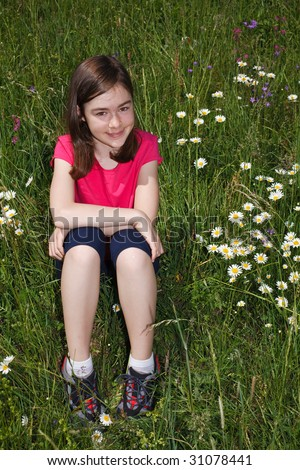 Girl sitting on green meadow
