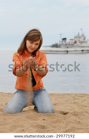 girl sitting on her knees at beach