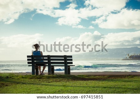 Girl sitting on park bench watching the sunset.