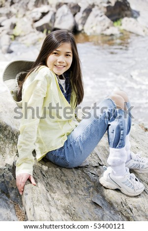Girl sitting on rock cliff edge over river