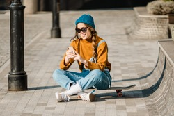 Girl sitting on skateboard and use mobile phone. Outdoors, urban lifestyle. cute skater girl sitting on skate board checking smart phone listening to music using internet and takes a photo.