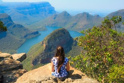 Girl sitting on stone on the cliff in the Blyde River Canyon, South Africa
