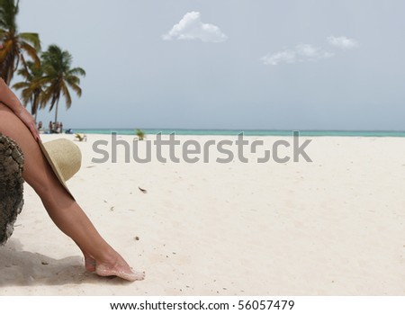 Girl sitting on the beach tree and holding a hat