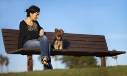 Girl sitting on the bench with her dog