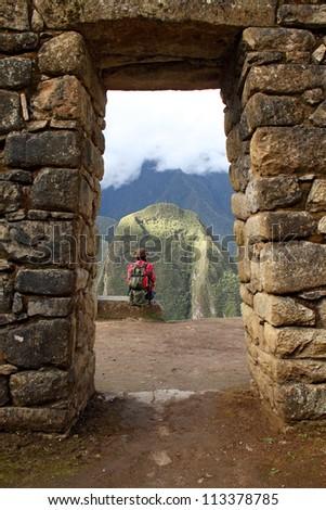 girl sitting on the edge of rock in a stone arch in Machu Picchu, Peru