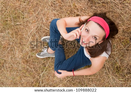 girl sitting on the grass and talking on cell phone