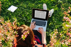 Girl sitting on the grass in a flowered garden work at a laptop