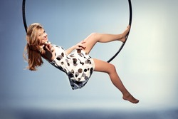 Girl sitting on the hoop and points the finger
