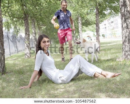 girl sitting on the lawn and her boyfriend with her ??Labrador ran