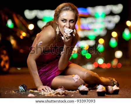 Girl sitting on the road and eating cake