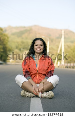Girl sitting on the road in mountain