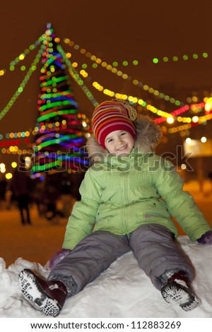 girl sitting on the snow and laughs, on the background of a Christmas tree