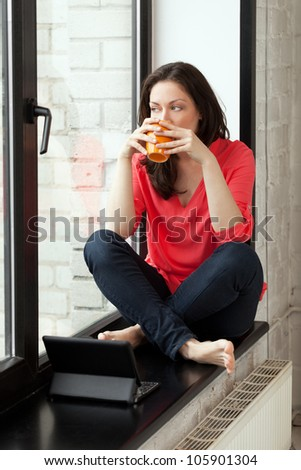 Girl sitting on windowsill with cup of tee and notebook