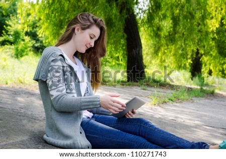 Girl sitting outdoors on a paved driveway in a verdant garden using a touchscreen tablet