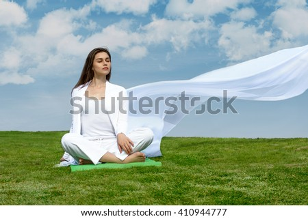 Girl sitting relaxed on the grass against the blue sky. She is wearing in a white loose clothes, which flutter in the wind. Concept: freedom, health, cleanliness.