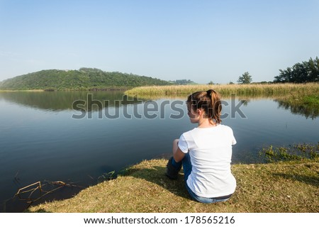 Girl Sitting River Water Lagoon Teen girl relaxing sitting by beach river lagoon waters on a calm blue day in the countryside