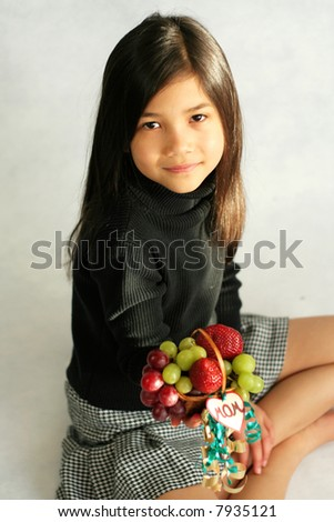 Girl sitting with fruit basket