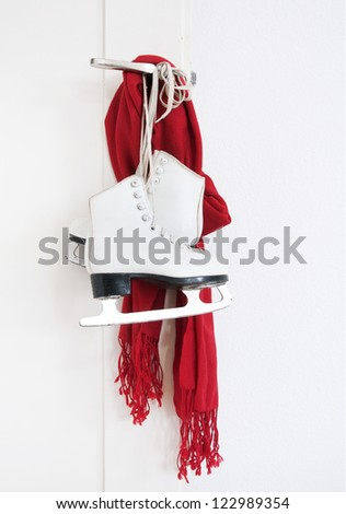 Girl skates and red scarf hanging on the door