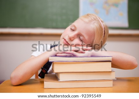 Girl sleeping on her books in a classroom