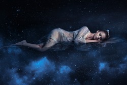 Girl sleeps in space among stars night sky fantastic fotoshoot creative color. dark blue northern lights. Sleeping Beauty Zodiac sign Galaxy Shine lights sparkle. young beautiful woman dream fantasy