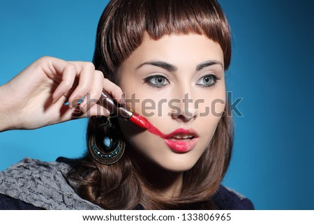 girl smearing lipstick on face