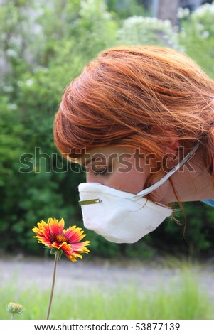girl smelling flower through protective mask