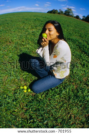 Girl smelling limes on a grass field.