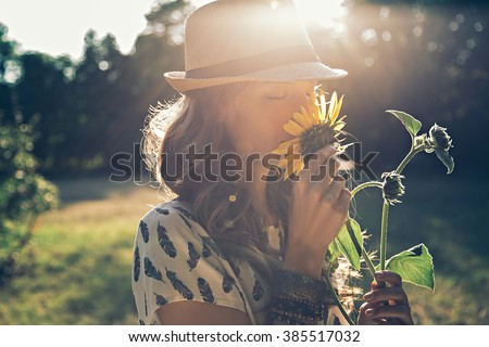 Girl smells sunflower in nature #385517032