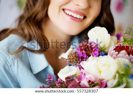 girl smiles a beautiful smile with white teeth. bouquet of flowers as a gift  for the holiday: birthday, Valentine's Day, wedding, anniversary. #557328307