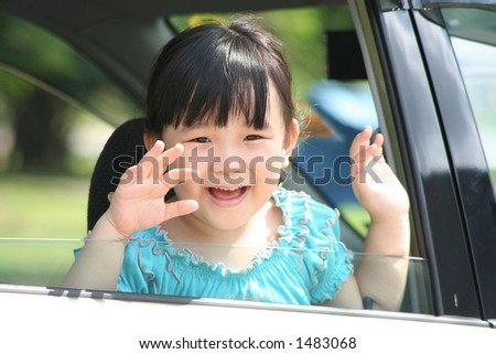 Girl smiling & waving goodbye in a car.