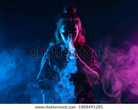 Girl smokes a VAPE on a dark background. Woman lets out clouds of smoke from an electronic cigarette. Girl stands in the middle of the frame and looks at the smoke from the e-cigarette. VAPE shops.