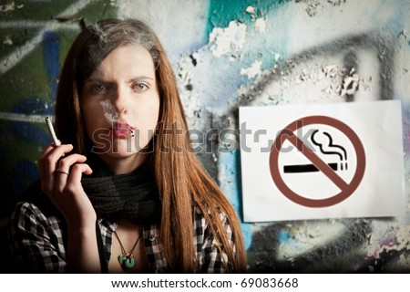 Girl smoking next to a no smoking sign in front of graffiti