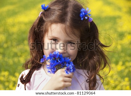 Girl sniffing some cornflowers