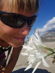 Girl sniffing white Sand lily. Flower is reflected in sunglasses. Blue sky in background.