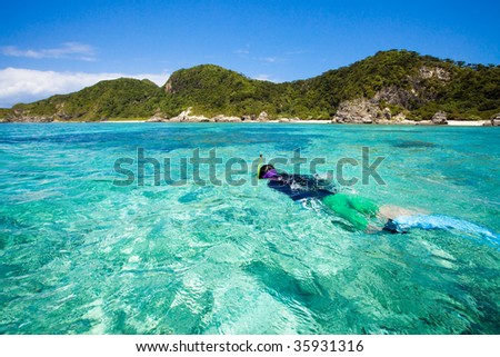 Girl snorkeling in clear blue water of Okinawa islands