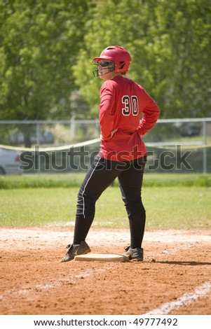 Girl softball player standing on base waiting for a play