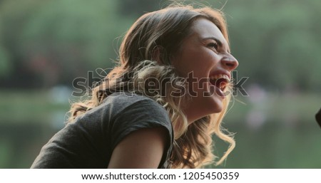 Photo of  Girl speaking to friend in conversation, burts laughing out loud to friend joke. Real life authentic smile and spontaneous laugh